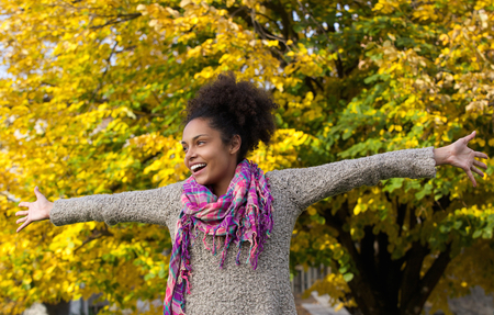 outstretched: Portrait of a cheerful young woman standing outdoors with arms outstretched