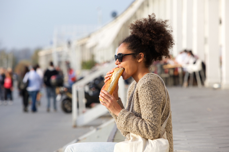 lunch break: Side view portrait of an attractive african american woman eating food outdoors Stock Photo