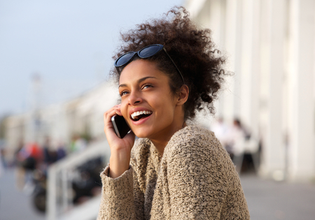 Close up portrait of a young woman smiling with mobile phone outdoors photo