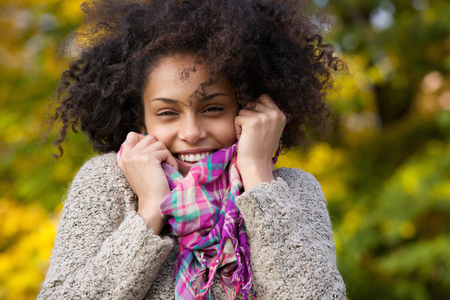 Close up portrait of a young woman laughing outdoors in autumn photo