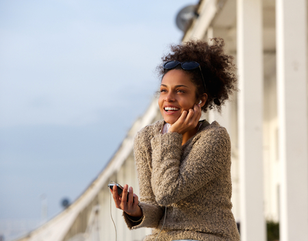 Close up portrait of a happy young woman listening to music on mobile phone photo