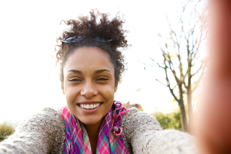 modelos negras: Retrato de una mujer joven sonriendo y hablando un Autofoto Foto de archivo