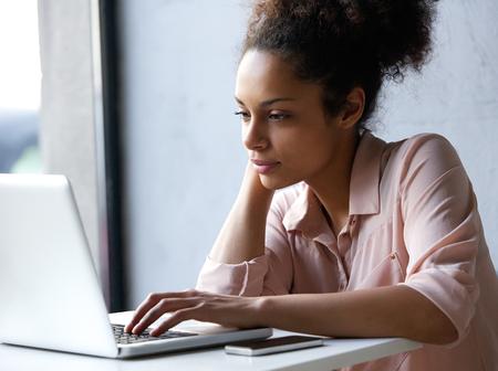 vrouwen: Close-up portret van een jonge zwarte vrouw op zoek naar laptop