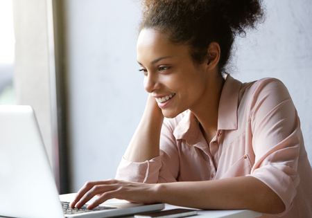 Feche acima do retrato de uma bela jovem, sorrindo e olhando para tela do laptop