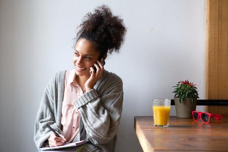 휴대 전화에 얘기하고 메모를 젊은 아프리카 계 미국인 여자의 초상화