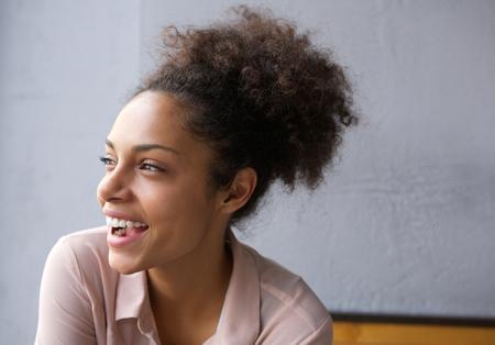 riendose: Retrato de perfil de una bella joven mujer afroamericana riendo