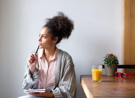 Retrato de una mujer joven sentada en casa con lápiz y papel