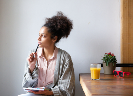 persona escribiendo: Retrato de una mujer joven sentada en casa con lápiz y papel