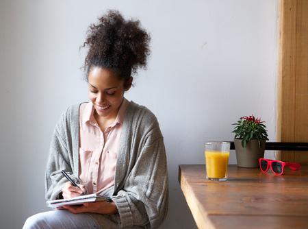 persona escribiendo: Retrato de una mujer sonriente escribiendo en bloc de notas en el hogar