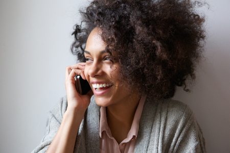 Close up portrait of a young woman laughing and talking on mobile phone photo
