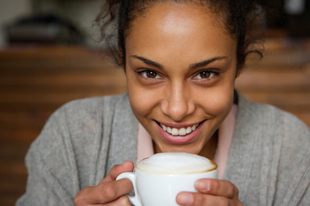 Close up portrait of a beautiful african american woman smiling with cup of a coffee photo