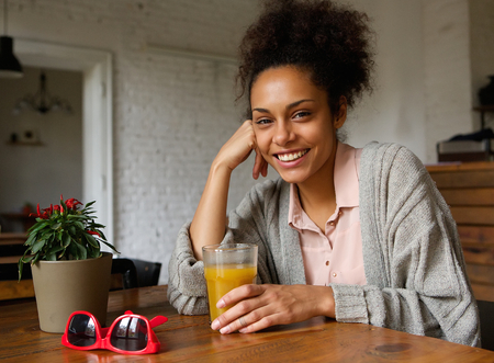 jugo de frutas: Close up retrato de una mujer joven y sonriente con un vaso de jugo de fruta Foto de archivo