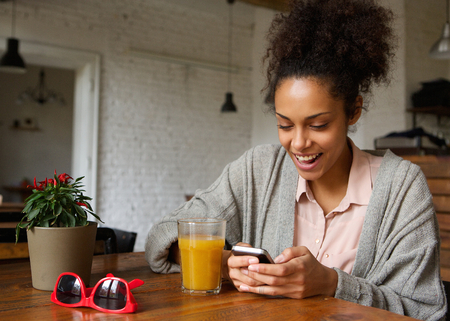 Close up portrait of a cheerful young woman typing a text message on mobile phone Stock Photo