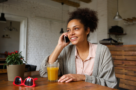 Close up portrait of a young woman smiling and talking on mobile phone photo