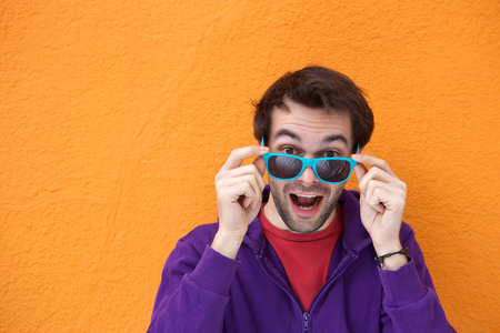 Fun fashion portrait of a young man laughing and holding sunglasses photo