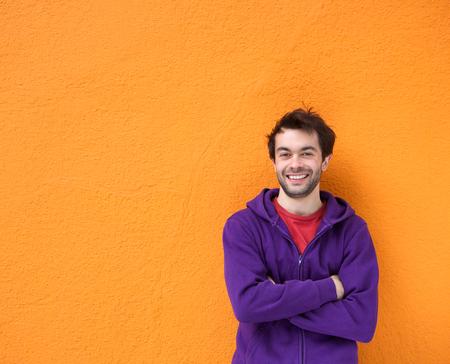Portret van een zelfverzekerde jonge man glimlachend met gekruiste armen