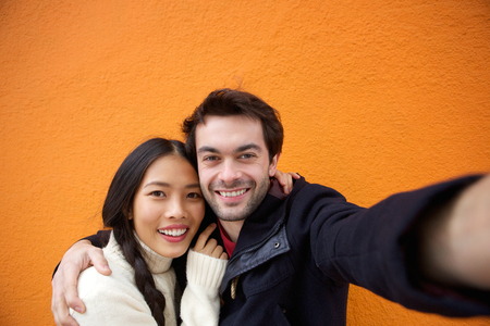 Close up portrait of a young man and woman smiling while taking selfie photo