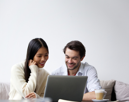 human relationship: Portrait of a happy young couple working on laptop at home Stock Photo