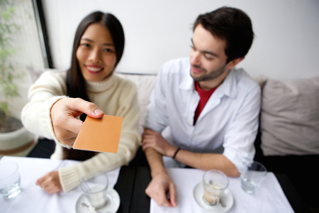 Portrait of a happy couple paying for meal with card at restaurant