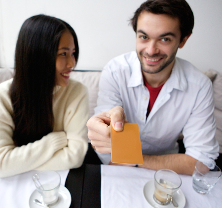 Portrait of a smiling couple paying for meal at restaurant photo