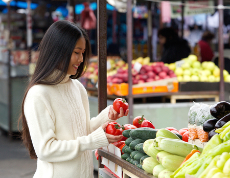 asian produce: Portrait of a beautiful young woman smiling at the vegetable market Stock Photo