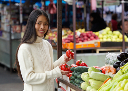 Portrait of a smiling young woman holding tomatoes at vegetable market photo