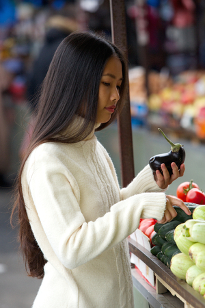 asian produce: Portrait of a young asian woman holding vegetables at market