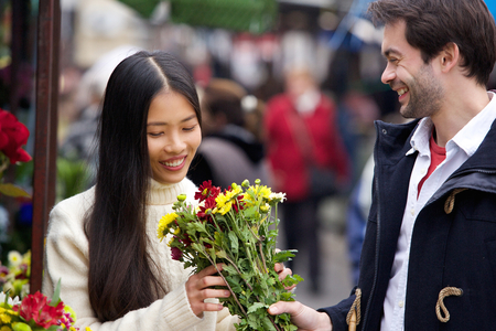 Portrait of a young man giving flowers to beautiful woman