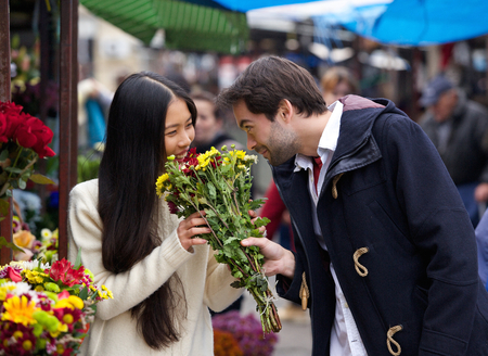 Portrait of a happy couple smelling flowers together photo