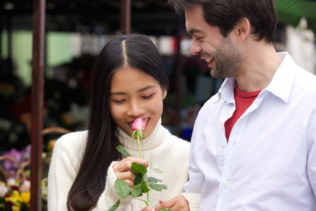 Close up portrait of a beautiful young woman smelling rose with boyfriend smiling photo