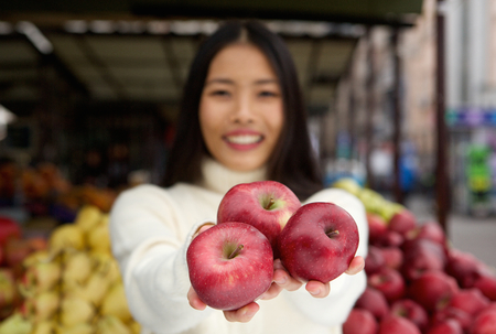 Close up portrait of a smiling young woman holding red apples in hand at market store photo