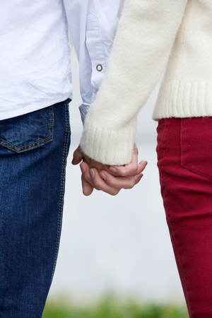 male hands: Back view of boyfriend and girlfriend holding hands outdoors