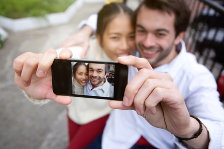 Portrait of a happy smiling couple taking selfie outdoors photo