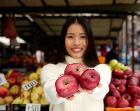 Close up portrait of an attractive young woman smiling with red apples at market store photo