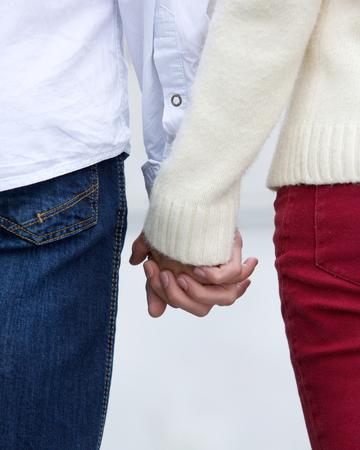 cogidos de la mano: Cierre de vista trasera retrato de una joven pareja cogidos de la mano