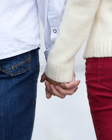 Close up rear view portrait of a young couple holding hands