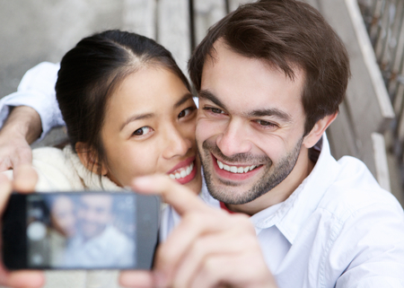 taking photograph: Close up portrait of a happy young couple taking a selfie and smiling