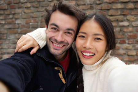 Close up portrait of a happy smiling young couple taking selfie photo