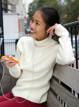 woman sweater: Close up portrait of a young woman sitting on bench with mobile phone and earphones