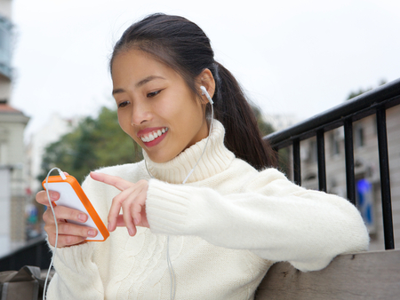 Close up portrait of a young asian woman smiling with cellphone and earphones photo