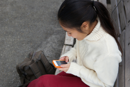 Close up portrait of a young woman sitting on bench sending text message on mobile phone photo