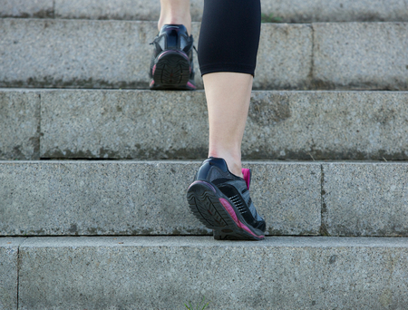 concrete stairs: Low angle rear view young sports woman walking upstairs in gym shoes Stock Photo