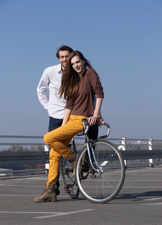 Portrait of a trendy young couple posing with bike outdoors photo