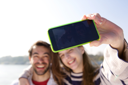 Close up self portrait of a happy young couple taking selfie with mobile phone photo