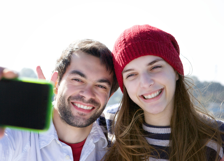 Close up portrait of a happy young couple smiling and taking selfie with mobile phone photo