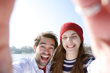 Close up portrait of a young couple having fun and taking selfie photo