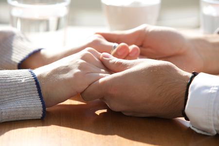 Close up male and female holding hands over table