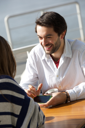 Portrait of a young man smiling and showing woman mobile phone at cafe photo