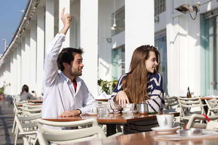 Portrait of a young man sitting at outdoor cafe with raised arm asking for waiter photo