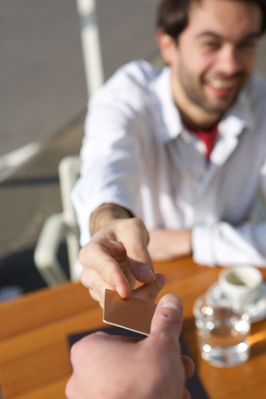 credit card bills: Close up portrait of a young man handing a waiter payment card at restaurant